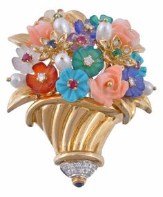 A multi gem set giardinetto brooch and ear clips suite, the swirling gold basket with a spray of foliate decoration set with a variety of carved flower heads of turquoise, coral, frosted rock crystal, and other gems, with variously cut gemstone centres including, rubies, emeralds, sapphires, 5cm long; together with a pair of matching ear clips en suite, with post and clip fittings, 2.6cm diameter