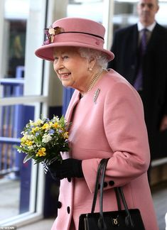Dressed in a pretty powder pink coat with black button detail, the Queen injects some Spring radiance into a grey Devon this morning as she arrived at Plymouth station to attend the decommissioning ceremony of HMS Ocean