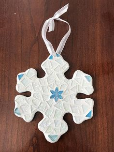This beautifully handcrafted stained glass mosaic snowflake ornament was made with care. The snowflake mosaic has been made with hand cut textured iridescent stained glass, mosaic cobblestones and a snowflake shaped glass tile. The glass has been adhered to sturdy mdf I cut with a