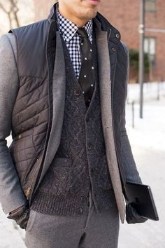 Shop this look for $641:  http://lookastic.com/men/looks/vest-and-dress-pants-and-gloves-and-dress-shirt-and-tie-and-cardigan-and-blazer/1517  — Charcoal Quilted Vest  — Grey Wool Dress Pants  — Black Leather Gloves  — Navy and White Gingham Dress Shirt  — Black and White Polka Dot Silk Tie  — Charcoal Knit Cardigan  — Grey Wool Blazer