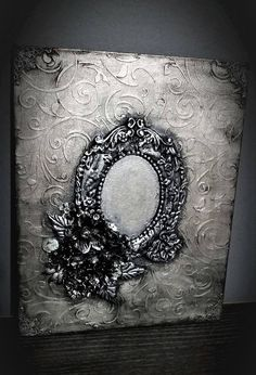 Silver and black acrylics. Big deautiful and detailed frame made of clay. Textured backround with stencil.