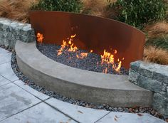 Nifty way to approach an open evening fire pit. Nicely done. A few chairs and a great place to rest your feet on that wall!