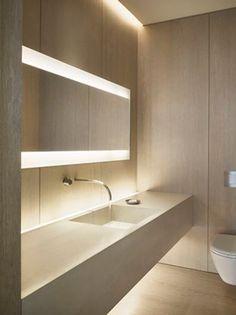 Baño iluminado con espejo con luces del arriba y abajo. Diseño recto y listo en color beige