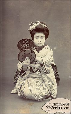 A maiko dressed for Miyako Odori. She's holding tsuzumi - a traditional Japanese hand drum