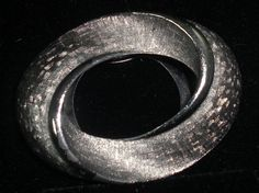 Vintage Silver Lieba Scarf Dress Clip. Oval shaped scarf, shirt or dress clip. Silver tone with brushed detail lines and think center surround. Fold up down clip on back. Marked Lieba USA on back under upper clip hinge.