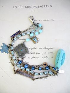 "3 Strands Baby Blues Bracelet with Princess Phone This 3 strand bracelet has a vintage, rhinestone bracelet for strand number one. It is a prong-set and has light blue stones set up high. I'm fairly certain the setting is sterling, too, as the clasp was stamped.   Strand number two is a made up of 3 different chains interrupted in two places by a vintage repurposed blue enamel link from a add-a-link catechism brooch and says ""third year""; the other interruption is a..."