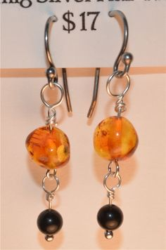 Orange Amber & Jet Earrings on Silver-plated Wire & Sterling SIlver Fish Hooks - $17. in my ETSY shop: www.ETSY.com/shop/harperscauldron.  Amber is a protective stone, which will cleanse and heal the aura. It is associated with the Sacral chakra, and helps to balance and cleanse the chakras. Jet is a protective stone, guarding against illness and violence. It helps with stability and balance. Amber is fossilized tree resin, and jet is fossilized wood. Together, they are very grounding.