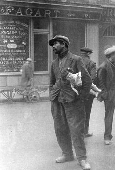 Destituate man standing in street near Les Halles holding a doll under his arm, Paris, 1930 - Alfred Eisenstaedt