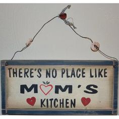 """There's No Place Like Mom's Kitchen"" Rustic Country Wood Plaque Sign with a Metal Wire for Hanging Which Holds Three Real Buttons 12 x 5 1/2 x 3/4 Inches. Two Small Metal Hearts Nailed to Wooden Sign"
