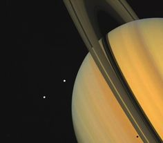 Two of Saturn's tiny moons can be seen in this impressive shot, along with the gas giant's rings.