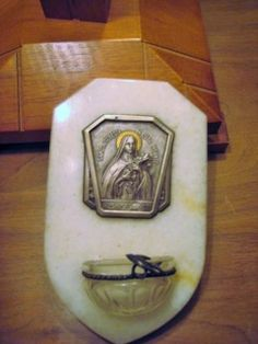 """Vintage souvenir holy water font  from the Basile of Saint Theresa. Measuring 6"""" wide by 3 5/8"""" wide.A 1/2"""" marble base with silver tone and brass Saint Therese plaque  along with the original holy water glass container. It has a sweet dove on a rolled decorative wire holder. Brass hanger on back. Just a beautiful Catholic treasure to decorate your religious nook or shrine."""