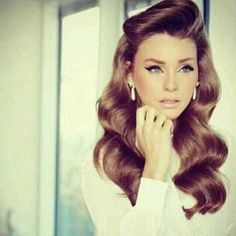 Late 60's-Early 70's neutral glam look. Nude lips-Bold winged eyeliner. Loose wavy hair.