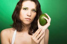 Woman Holding a Green Avocado