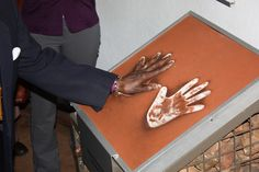 Archbishop Emeritus Desmond Tutu places his hand in the hand prints of Nobel laureate, former South African president Nelson Mandela. He visited Maropeng on July 31