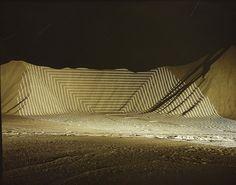 Jim Sanborn utilise un projecteur puissant pour dessiner des formes géométriques sur des paysages qu'il photographie de nuit.