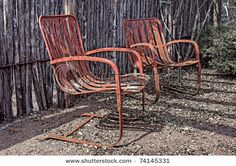 -two-old-rusty-red-chairs-next-to-a-rustic-fence.