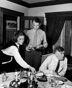 Jimmy Stewart, home from the war, helps clear the table at his parents' house, 1945.