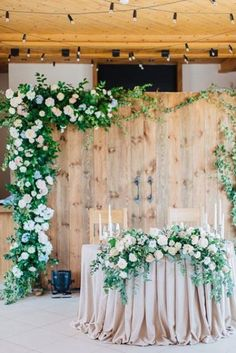 old barn doors decorated with lush blooms and foliage look cute and rustic #weddingbackdrops