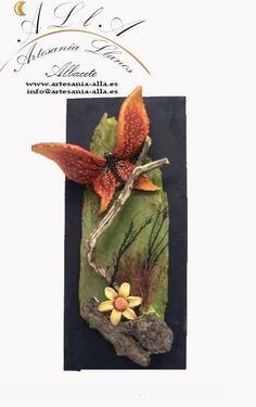 Cuadro madera mariposa y flor. Material empleado: Madera natural y los motivos en pasta cerámica. Pintado a mano. Libre elección de los colores y motivos. Precio: 50 € www.artesania-alla.es