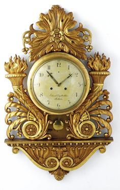 A SWEDISH GILTWOOD CARTEL CLOCK,  CIRCA 1825  the painted dial signed Eduard Engelbrechten, Stockholm, flanked by scrolling foliate torches on an anthemion carved bracket.