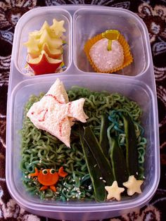 """Little angel fish tuna sandwich is swimming in colored Top Ramen with a carrot crab and apple starfish. Smaller compartments are filled with apple starfish and a Taro Mochi. Photo credit: A Pocket Full of Buttons  <a href=""""http://bit.ly/98glde"""">http://bit.ly/98glde</a>"""