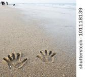 hand prints on the sand by hxdbzxy, via Shutterstock
