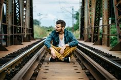 Portrait of young man sitting on the railroad bridge - Portrait of young man sitting on the railroad bridge. Vintage Instagram style effect, soft and selective focus, shallow DOF, grain texture visible on maximum size