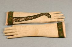 Pair of womens' long gloves, circa 1735, of white leather, flesh side outwards but glazed, inset with curving bands of dark green cobweb like needlepoint lace and edged with green braid, 38 cm long. Fashion Museum, Bath.