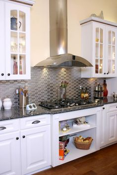 Elegant kitchen design with open cabinets below the gas stove top and patterned stainless steel tile backsplash metallic finish also white wooden cabinet with blue pearl granite countertop
