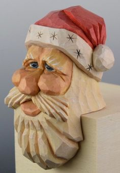 Santa will have an ideal perspective sitting atop your mantle or bookcase. NO good or bad deed will be missed. This clever old elf sits daringly on the edge to catch everyone in the act. He sits 3 inches (7.6 cm) tall and his beard hangs over 2.5 inches (6.4 cm) for an overall height of 5.5 inches (14 cm). Santa is hand carved with love from a single piece of Northern Basswood.