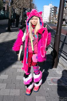 Jan 2014: Mekiru's look features a pink faux fur monster hoodie from the Japanese brand Superlovers over a pink t-shirt with a print skirt from Spinns, striped tights, furry leg warmers from Spinns, and colorful Yosuke platform shoes. Accessories include a hat with ears, necklaces from Broken Doll & Spinns, a Rock 'n' Roller Coaster guitar bag, and a Sega controller bag from Galaxxxy.