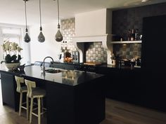 Landelijk zwarte keuken met schouw. Metallic tegeltjes.