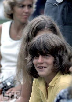 John Jr. at Age 14  Wearing braces and long hair in 1974, John Jr. attends a celebrity tennis tournament named after his uncle Robert.