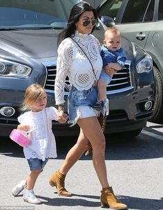 Kourtney Kardashian wearing a Crochet top with shorts and camel suede booties