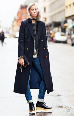 Long coat with gold buttons, striped top, and cuffed skinny jeans