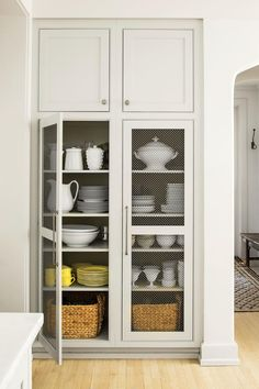 Open shelving is an excellent feature for showing off all your prettiest china and serving pieces. In this case, a chicken wire screen helps soften the graphic effect of the built-in display.     Love it? Get it!  Cabinet paint: Gray Owl (2137-60)