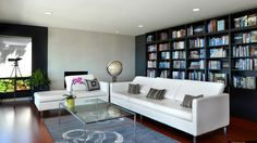 Bright and sophisticated, this contemporary living room features a wall of built-in bookshelves and white leather sofas surrounding a glass coffee table. Warm wood floors complete the elegant design.
