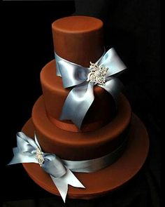 Classy chocolate brown three tier wedding cake decorated with blue satin bows and diamontee brooches. From www.cakesbyfrancesca.com.au
