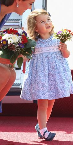 Princess Charlotte in a pretty floral frock, teamed with white ankle socks and navy shoes. The young Princess was happy to received her own adorable miniature bouquet as they arrives at Berlin Tegel Airport.