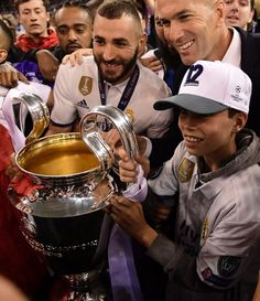 Real Madrid's French coach Zinedine Zidane (c), his son Elyaz and Real Madrid's French striker Karim Benzema (L) pose with the trophy after Real Madrid won the UEFA Champions League final football match between Juventus and Real Madrid at The Principality Stadium in Cardiff, south Wales, on June 3, 2017. / AFP PHOTO / JAVIER SORIANO