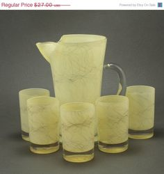 Wonderful drizzle pitcher in a pale yellow with gold scribbles, includes 5 matching glasses. Use to serve juice or your favorite cocktail.  Pitcher