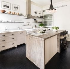 Some beautiful elements combine to make the most of this compact kitchen space. Reclaimed Douglas fir island bench, cabinets either side of the cooker modelled after Victorian chest of drawers, a wall
