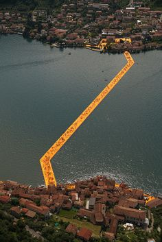 """""""The Floating Piers"""" is a temporary, public art installation by artists Christo and Jeanne-Claude that is currently on display on top of Lake Iseo in Lombardy, Italy. Its vibrant, yellow walkways are constructed with square meters of fabric,. Christo Floating Piers, Christo Y Jeanne Claude, Art Public, Walk On Water, Environmental Art, Installation Art, Interactive Installation, Landscape Architecture, Around The Worlds"""