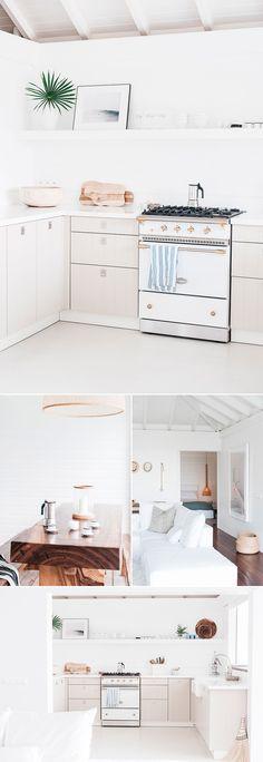 Chalé Paradisíaco com decoração clean, cozinha branca, sofá branco, mesa de madeira.