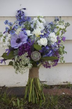 Wildflower rustic bouquet of blue delphinium, white Ranunculus, succulents, purple Anemone, white Stock, Queen Anne's Lace, purple Allium. Handle wrapped in twine. - Design by J. Morris Flowers
