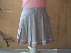 Vintage tennis pleated skirt. Tail Brand. Size 6 Soft grey with small print of pink, yellow, coral and blue squares and white Xs. Trimmed with 2 tones of pink ribbon. Zipper and button at the back.  Condition; Great vintage condition. Used. No defects or issues noted. Very clean. Freshly laundered.  Tag: Tail. Size 6. Made in USA. 100% Polyester Microfiber. Machine Wash Cool. Gentle Cycle. Tumble Dry. Cool Iron.  Measures: Waist: 28 ( 71 cm ) Hips: 39 ( 99 cm ) Length: 15 ( 38 cm )