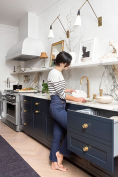 modern farmhouse kitchen design with navy kitchen cabinets and white kitchen cabinets, kitchen open shelf decor and modern pendant over kitchen island wiht leather barstools and range hood and mable backsplash