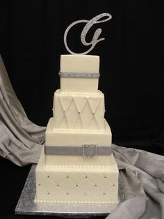 Showing off some bling with this white and silver wedding cake, complete with bejeweled initial topper and belted fondant accessories. @PartyFlavors #PartyFlavors