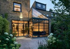 Blee Halligan Architects has renovated and extended a house on Highbury Hill in north London, using black gridded glazing and pale brickwork to frame views into the back garden.