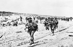 US troops passing along the shore edge in the path of armored vehicles, Normandy, 6 June 1944.